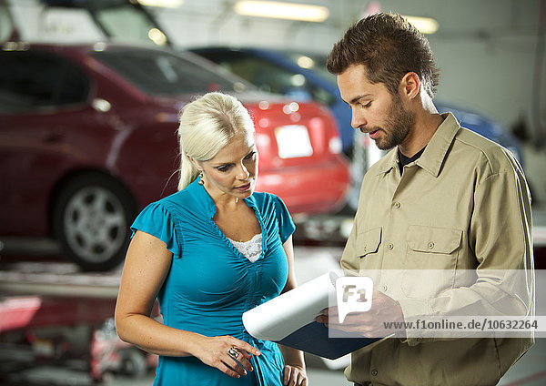 Mann und Kunde in der Reparaturwerkstatt besprechen Checkliste