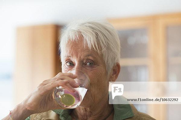 Porträt einer weißhaarigen Seniorin  die ein Glas Wasser trinkt.