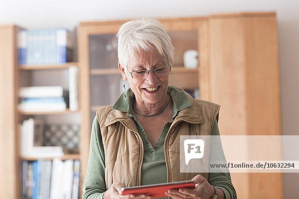 Porträt einer weißhaarigen Seniorin beim Betrachten ihres digitalen Tabletts zu Hause