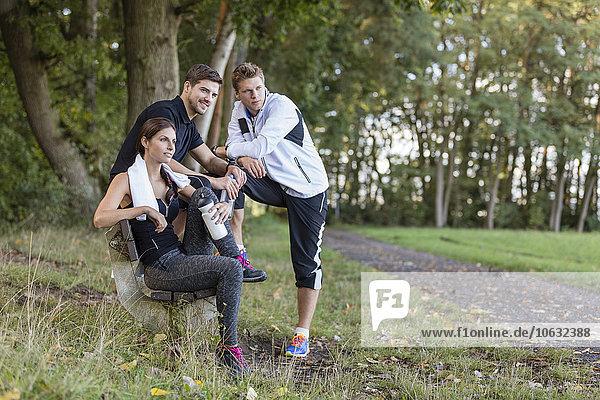 Sportler  die sich auf einer Parkbank ausruhen