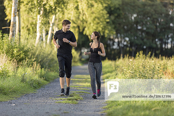 Man and woman jogging on rural path