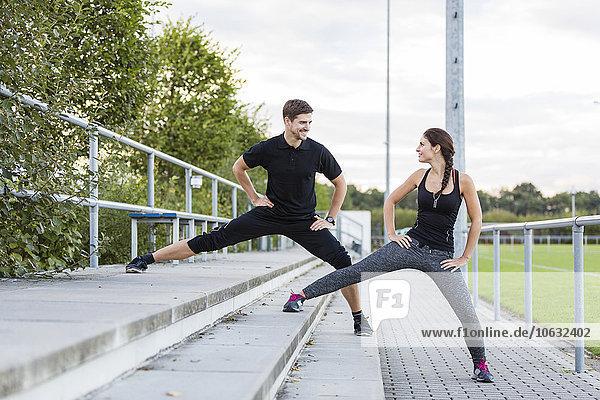 Mann und Frau beim Dehnen auf dem Sportplatz