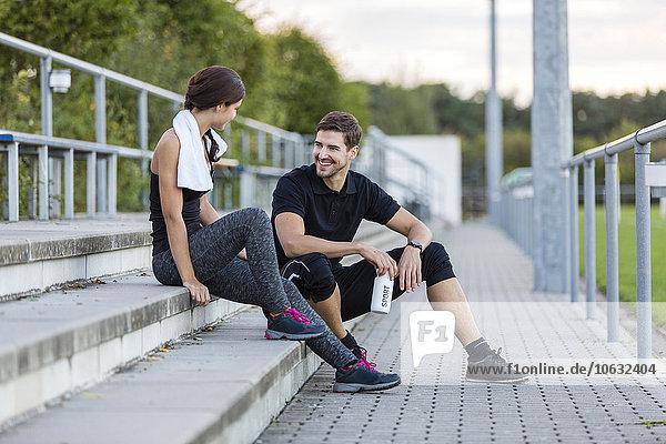 Sportlicher Mann und Frau im Gespräch auf dem Sportplatz