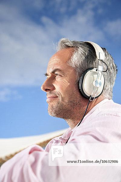 Porträt eines reifen Mannes mit Stoppelhörmusik mit Kopfhörer Porträt eines reifen Mannes mit Stoppelhörmusik mit Kopfhörer