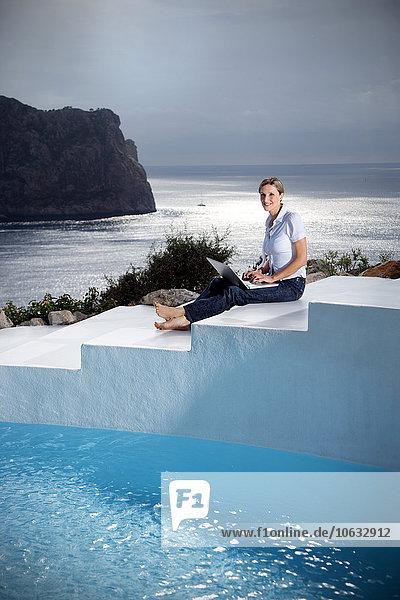Spanien  Mallorca  Frau mit Laptop auf einer Treppe neben einem Swimmingpool mit Meer im Hintergrund
