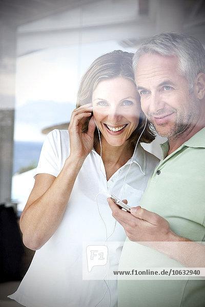 Portrait eines lächelnden Paares mit Kopfhörern und mp3-Player durchs Fenster schauend Portrait eines lächelnden Paares mit Kopfhörern und mp3-Player durchs Fenster schauend