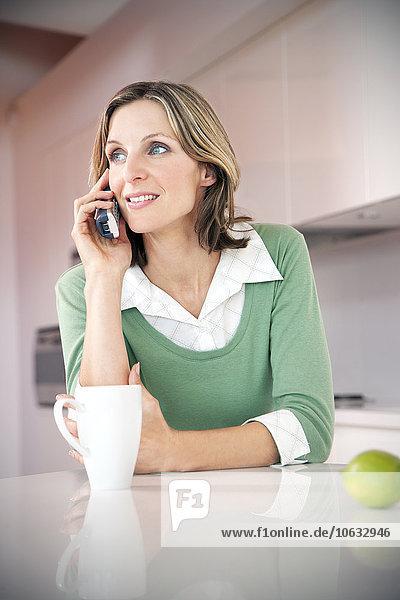 Porträt einer lächelnden Frau beim Telefonieren in der Küche Porträt einer lächelnden Frau beim Telefonieren in der Küche