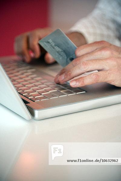 Mann mit Laptop und Kreditkarte  Nahaufnahme