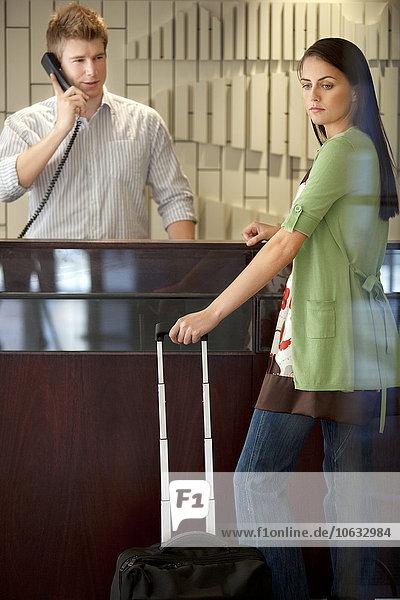 Frau stehend an der Hotelrezeption mit Rollkoffer Frau stehend an der Hotelrezeption mit Rollkoffer