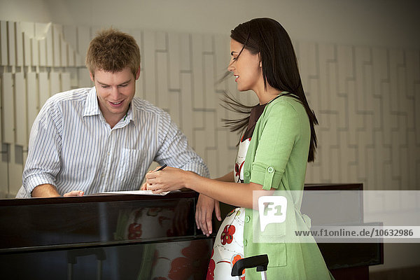 Frau an der Hotelrezeption Unterschriftsdokument Frau an der Hotelrezeption Unterschriftsdokument