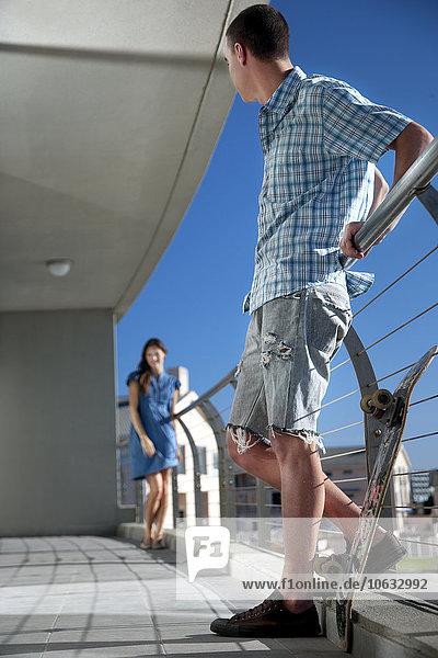 Junger Mann mit Skateboard auf dem Balkon mit Blick auf die Frau Junger Mann mit Skateboard auf dem Balkon mit Blick auf die Frau