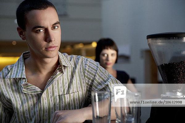 Porträt eines jungen Mannes am Tresen mit Frau im Hintergrund