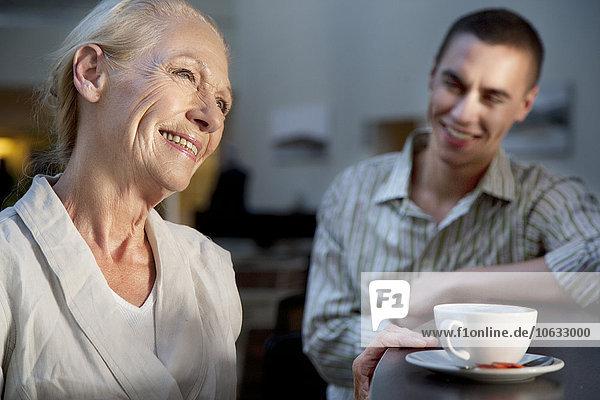 Lächelnde Seniorin mit Tasse Kaffee und jungem Mann im Hintergrund