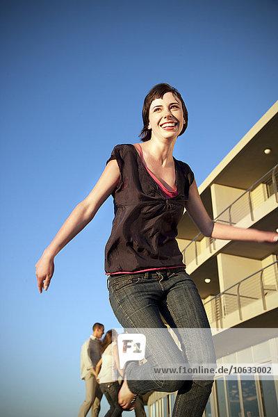 Glückliche junge Frau läuft mit Freunden im Hintergrund Glückliche junge Frau läuft mit Freunden im Hintergrund