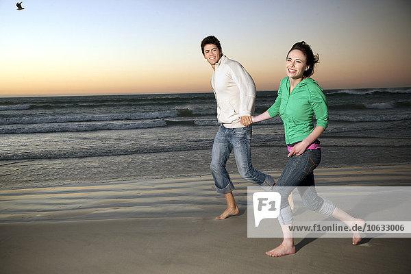 Junges Paar  das in der Abenddämmerung Hand in Hand am Strand läuft. Junges Paar, das in der Abenddämmerung Hand in Hand am Strand läuft.