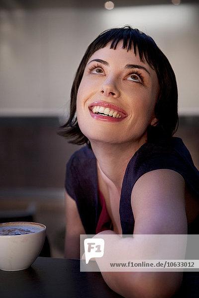 Lächelnde junge Frau mit einer Tasse Kaffee  die nach oben schaut. Lächelnde junge Frau mit einer Tasse Kaffee, die nach oben schaut.