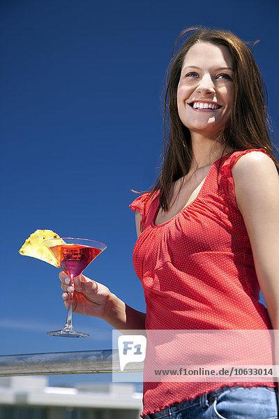 Lächelnde junge Frau im Sonnenschein mit Getränk Lächelnde junge Frau im Sonnenschein mit Getränk