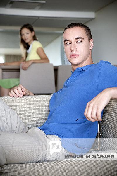 Junger Mann sitzt auf der Couch mit Frau im Hintergrund