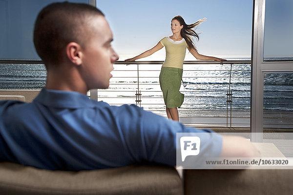Junger Mann auf Couch mit Freundin auf dem Balkon am Meer stehend Junger Mann auf Couch mit Freundin auf dem Balkon am Meer stehend
