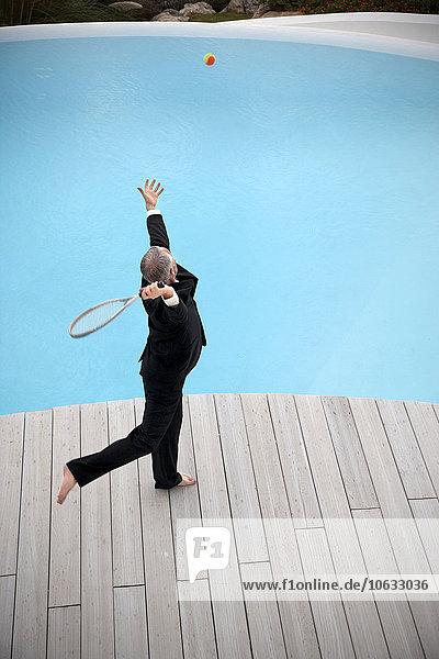 Barfuss Geschäftsmann im schwarzen Anzug mit Ball und Schläger vor dem Schwimmbad Barfuss Geschäftsmann im schwarzen Anzug mit Ball und Schläger vor dem Schwimmbad