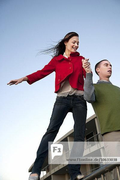 Junger Mann unterstützt Freundin beim Balancieren am Geländer Junger Mann unterstützt Freundin beim Balancieren am Geländer