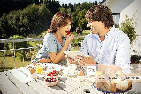 Glückliches Paar beim Frühstück auf dem Balkon
