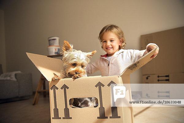 Lächelndes Mädchen mit Hund im Karton