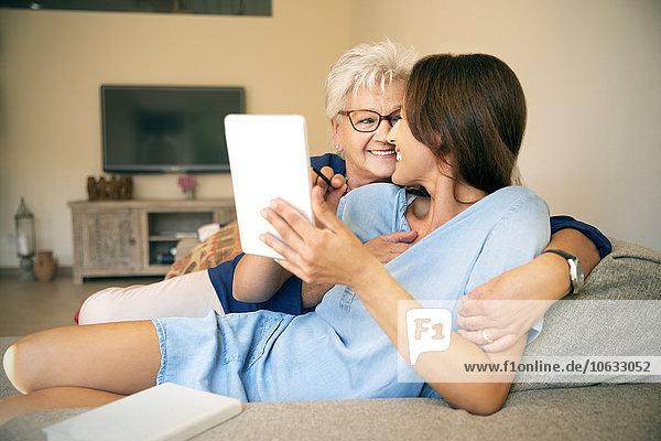 Glückliche Seniorin und erwachsene Tochter auf der Couch mit digitalem Tablett