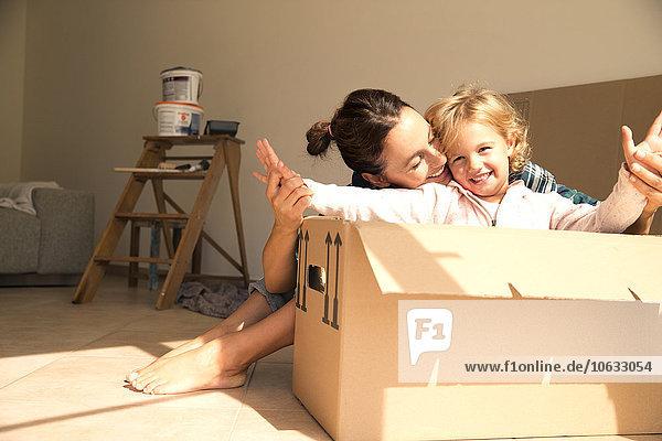 Glückliche Frau mit Tochter im Karton sitzend