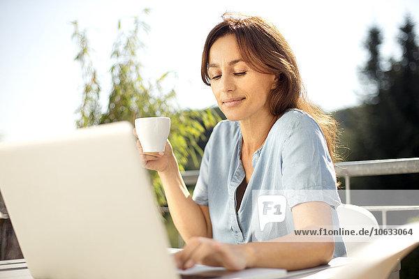 Frau auf dem Balkon mit Laptop