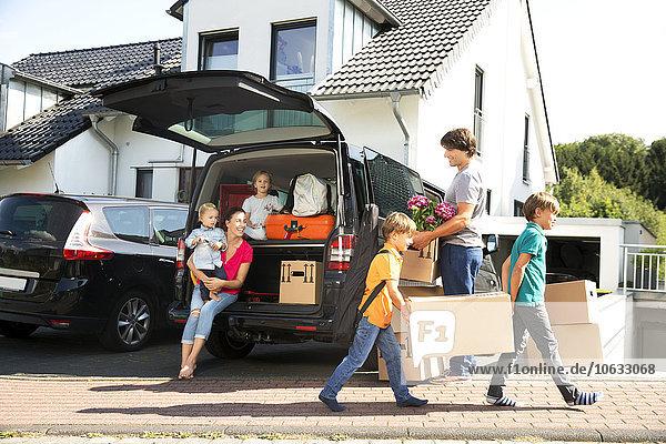 Glückliche Familie an der Einfahrt mit Pappkartons