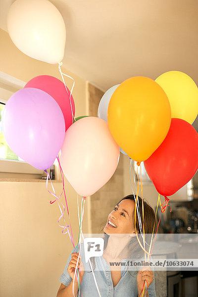 Fröhliche Frau steht und hält bunte Luftballons.