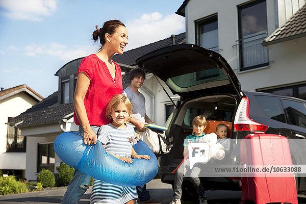Glückliche Familie mit schwimmendem Reifen in der Einfahrt