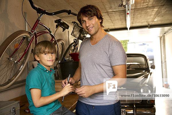Vater und Sohn in der Garage mit Oldtimer und Werkzeug
