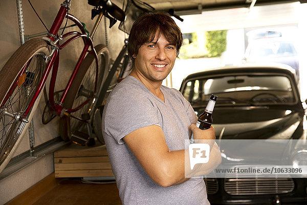 Lächelnder Mann in der Garage mit Bierflasche und Oldtimer