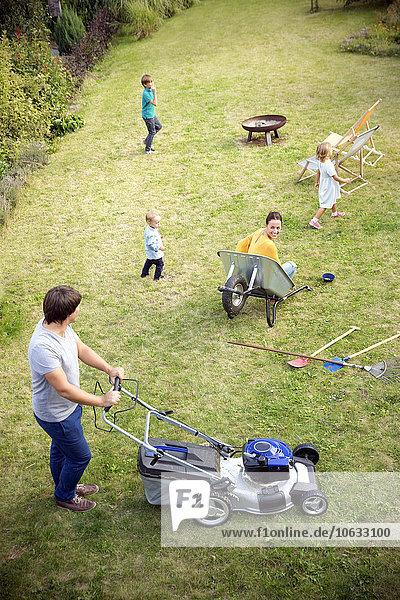 Vater mäht den Rasen im Garten und die Familie spielt im Gras.
