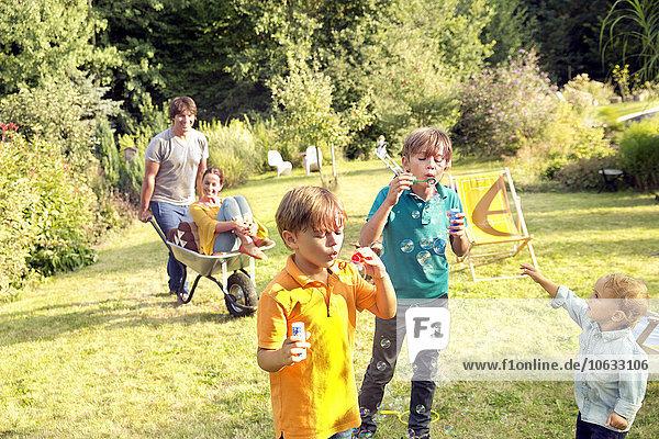 Glückliche Familie im Garten mit Mann  der Frau in Schubkarre schiebt und Jungen  die Seifenblasen blasen.