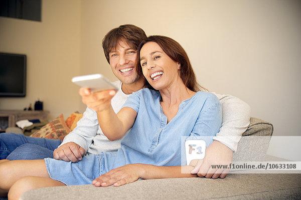 Lächelndes Paar auf der Couch beim Fernsehen
