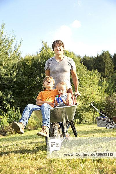 Vater schiebt zwei Söhne in Schubkarre in den Garten