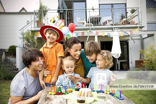 Glückliche Familie beim Kindergeburtstag im Garten