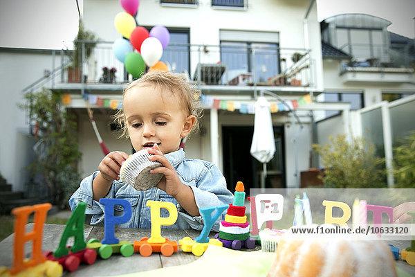 Glückliches Kleinkind feiert Geburtstag im Garten