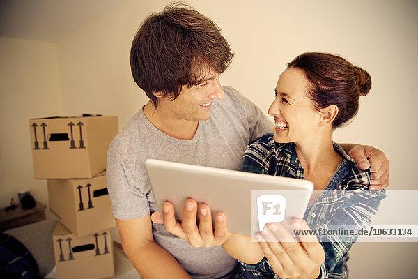 Glückliches Paar mit digitalem Tablett und Kartons im Hintergrund