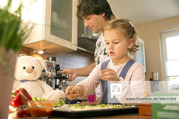 Vater und Tochter in der Küche bei der Zubereitung der Pizza
