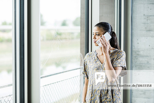 Young woman on cell phone looking out of window