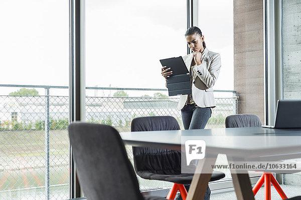 Junge Frau mit digitalem Tablett im Büro am Fenster