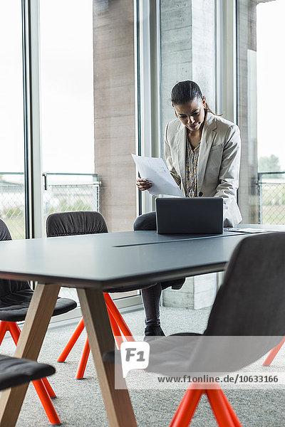 Junge Frau im Konferenzraum mit Unterlagen am Laptop