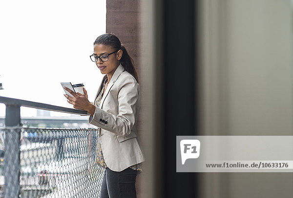 Junge Frau auf dem Balkon mit Kaffee zum Mitnehmen und Handy
