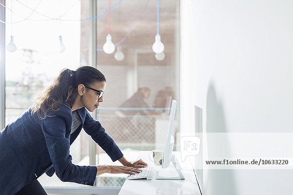 Junge Frau im Büro arbeitet am Computer