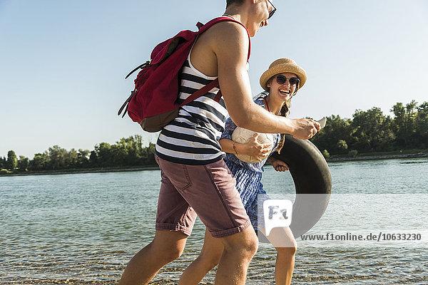 Junges Paar mit Schlauch und Handy beim Spaziergang am Flussufer