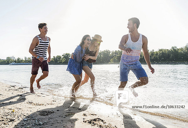 Happy friends running at the river